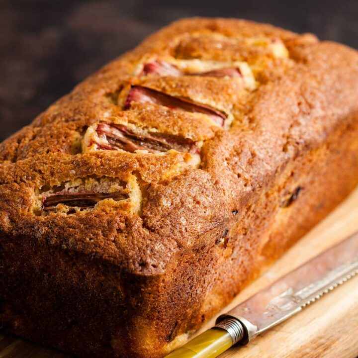 rhubarb and ginger loaf cake on a wooden board.