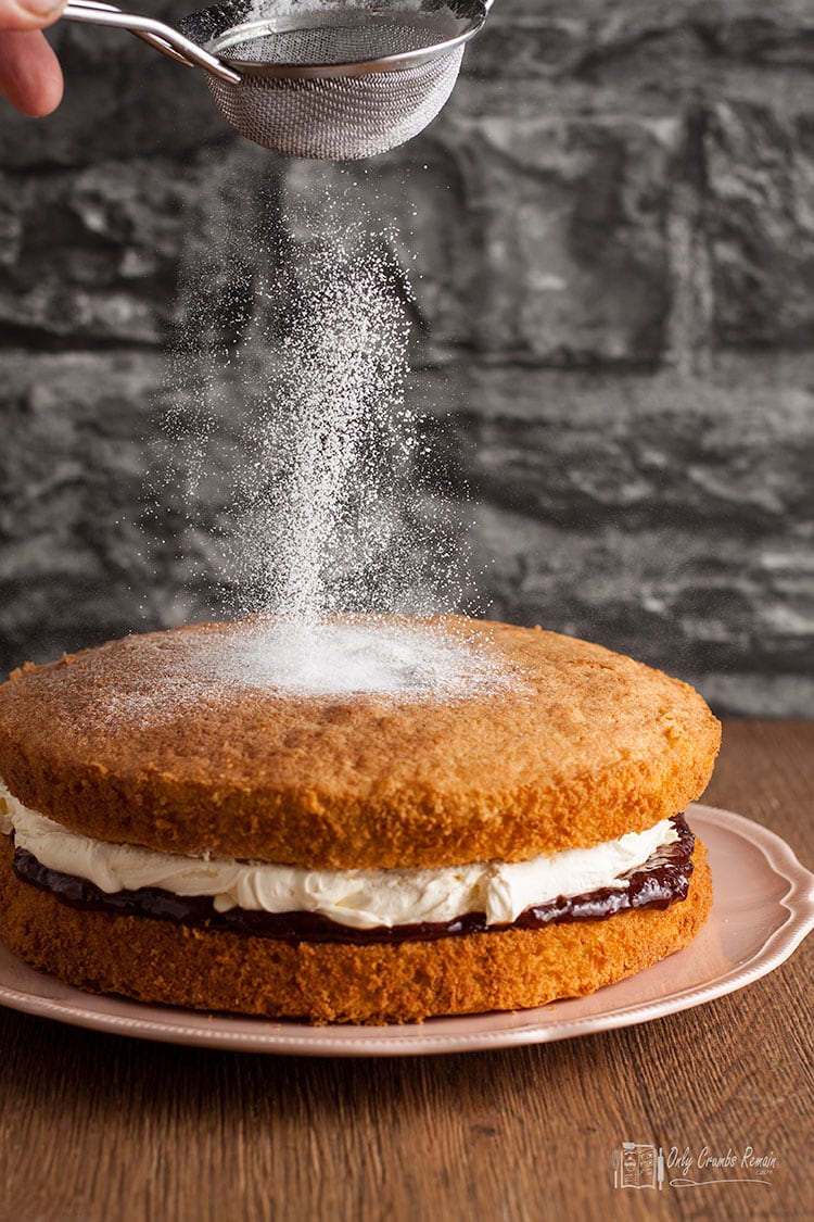 sifting icing sugar onto the cake.
