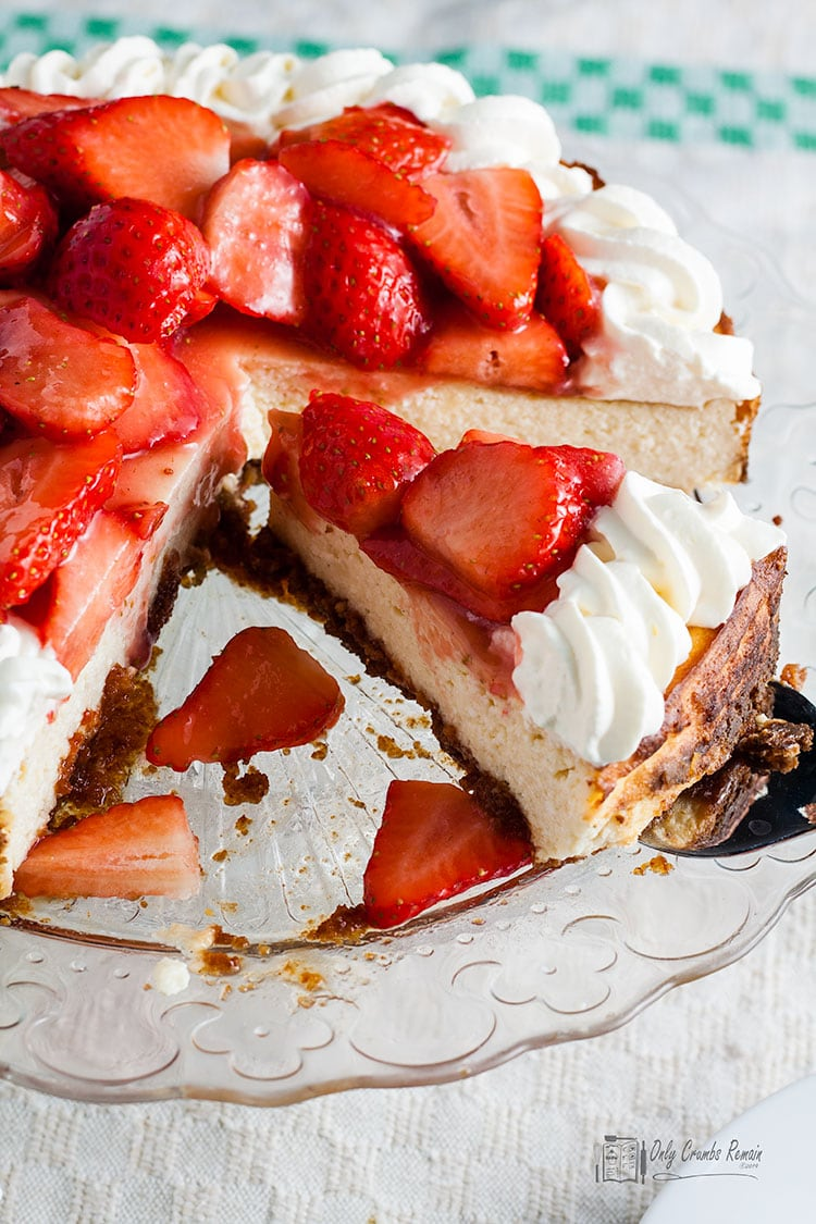 easy baked strawberry cheesecake on cake stand with slice being removed.