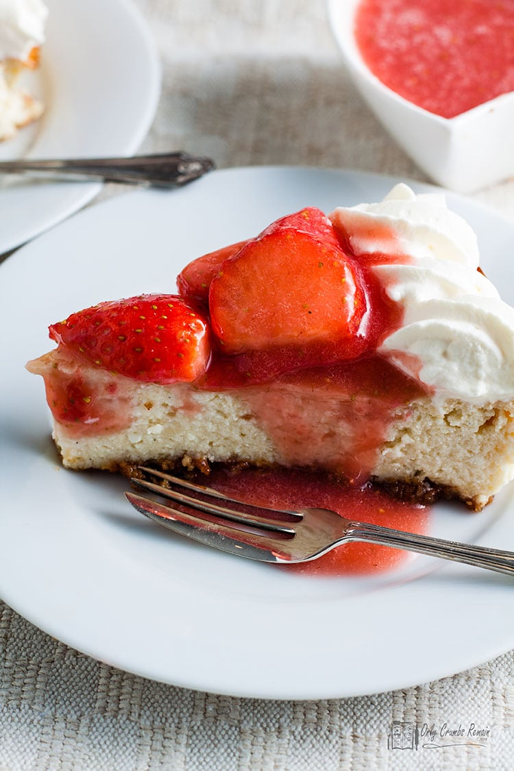 slice of easy baked strawberry cheesecake with strawberry coulis poured over.