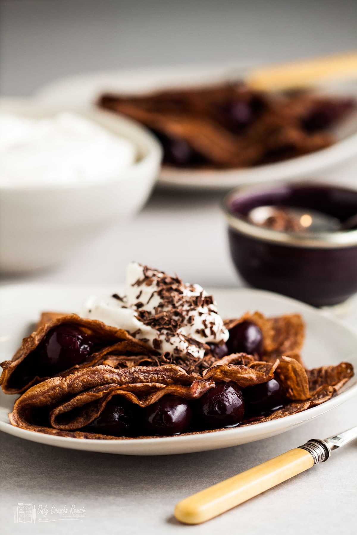 black forest pancakes on a plate with bowl of cream and chocolate behind.